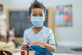 istock 5 year old boy wearing a mask at daycare 1255842608