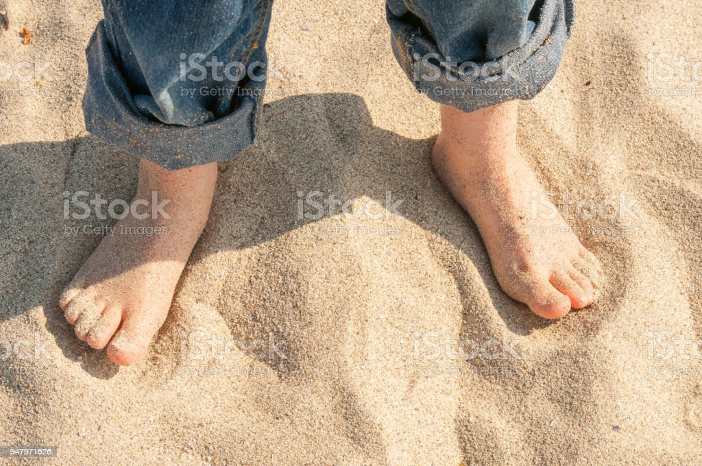 5 year old boys bare feet on sandy beach with rolled up jeans – zdjęcie