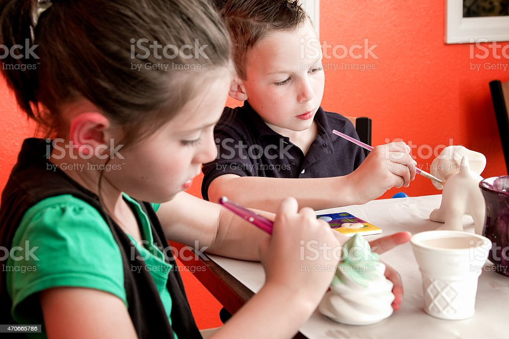 8 Year Old Caucasian Girl and Boy Painting Pottery stock photo