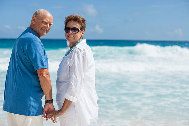65 year old couple beach - 60 69 years stock photos and pictures