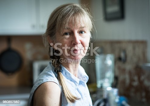 retirement age woman doing home improvement standing in a kitchen and background showing kitchen in state of being remodeled. Active lifestyle. Independence. Retirement goals and financial planning. Cute face with bold hair, bangs, and braid over shoulder.