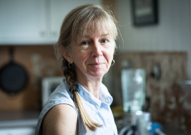 60 year old cute petite woman with natural light in kitchen - real people stock pictures, royalty-free photos & images