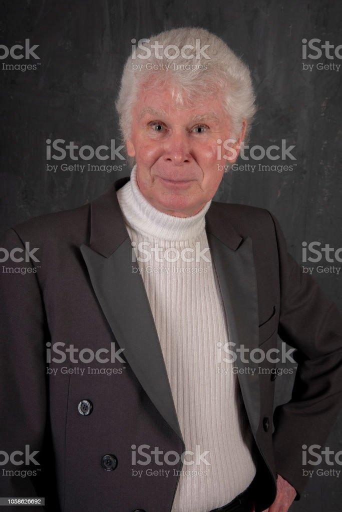 70 year old elegant man with white hair smiles at camera. stock photo