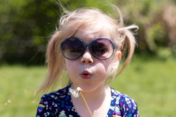3 Year Old Girl Blows Dandelion Seeds 1 – zdjęcie