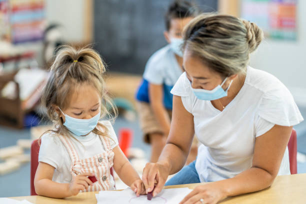 3 year old girl colouring at daycare wearing a mask stock photo