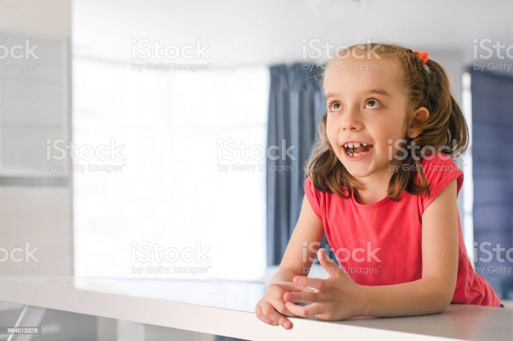 6 year old girl dreams of sitting at home table - Royalty-free Beauty Stock Photo