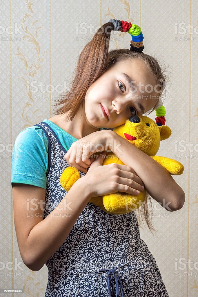 11 year old girl gently huggs her yellow toy bear stock photo