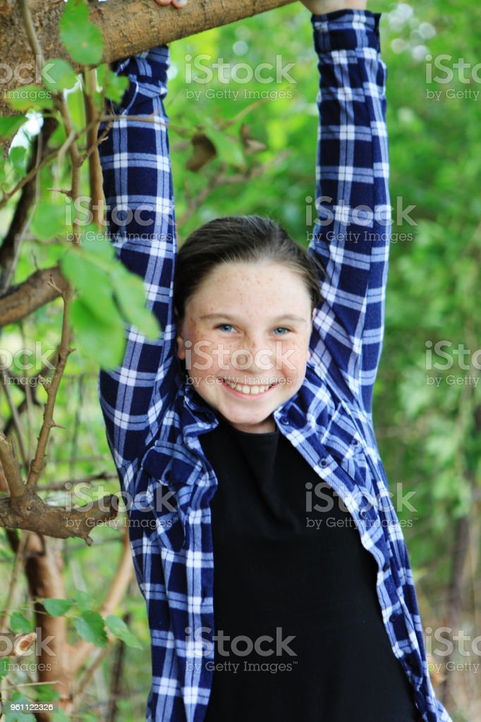 10 year old girl hanging from a tree branch stock photo