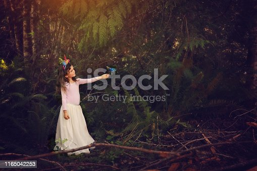 Little girl in a forest with her hand outstretched for a butterfly while sunlight shines down onto her.