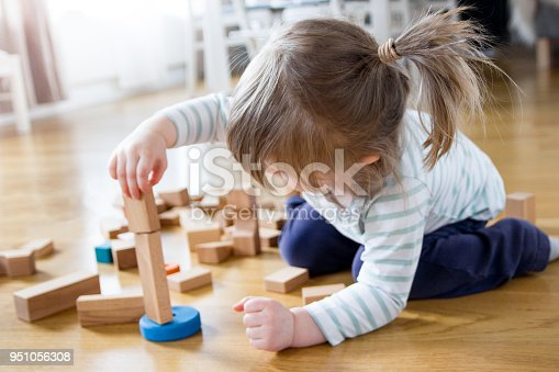 istock 2 year old girl is playing and building a tower of wooden toy blocks 951056308