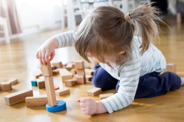 2 year old girl is playing and building a tower of wooden toy blocks 2 year old child is playing on the floor at home. She is building a tower of wooden toy blocks and are fully concentrated on balancing a piece on the top. 2 3 years stock pictures, royalty-free photos & images