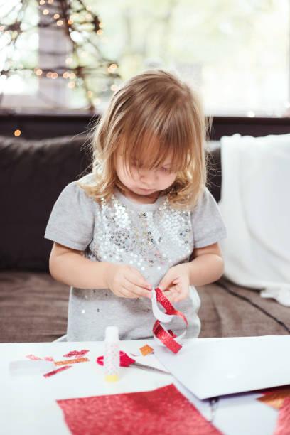 3-jähriges mädchen machen eine weihnachtsgirlande mit rotem glitzer-papier. - basteln mit kindern weihnachten stock-fotos und bilder