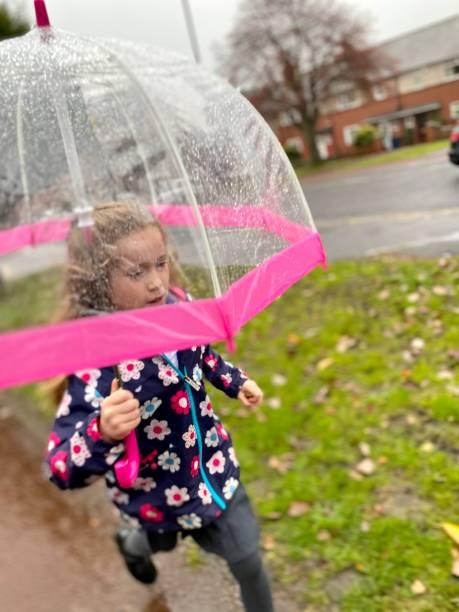 6 year old girl running to school in the rain stock photo