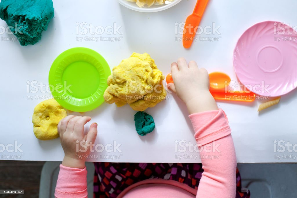 A 1.5 year old girl sits at a table and plays with a color test, on...