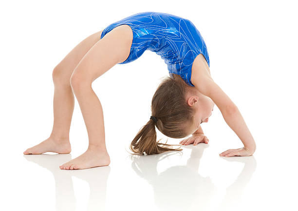 4 year old gymnast doing a bridge exercise stock photo