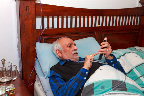 A 72 Year Old Indian Man Seen Recovering In His Bed At Home After His Laparascopic Gallbladder Surgery; He Is Very Busy Texting On A Smart Phone. stock photo