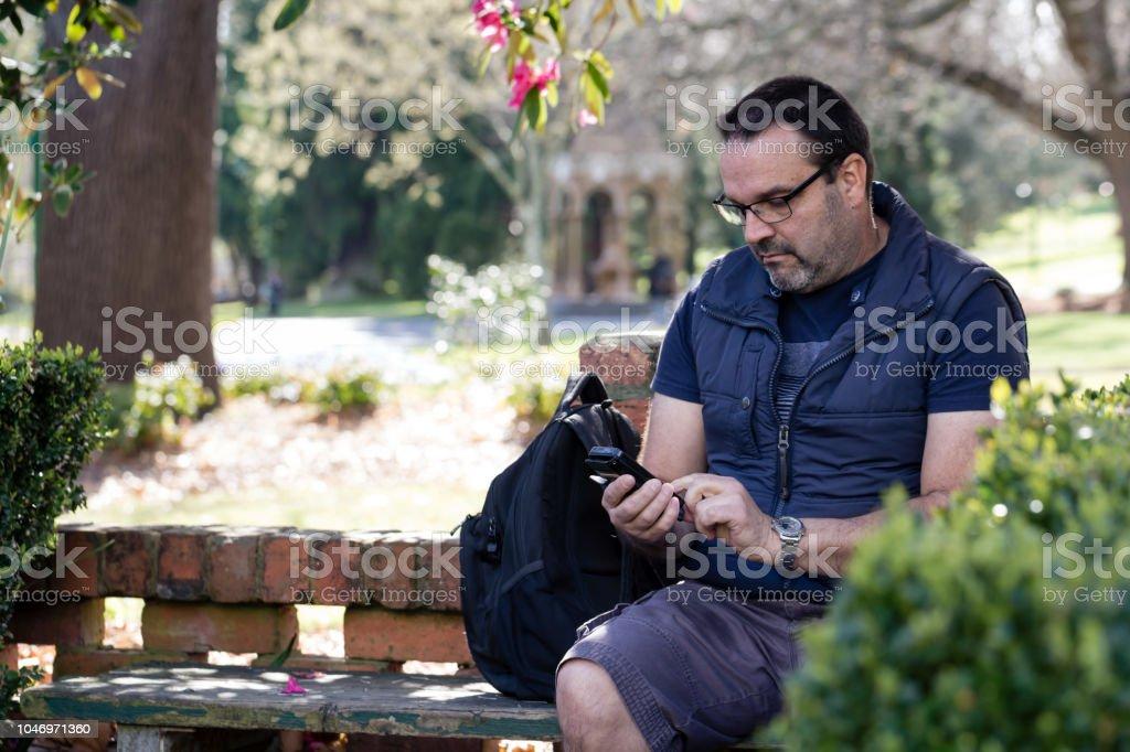 cep telefonunu kullanarak bir parkta 50 yaşındaki adam stok fotoğrafı