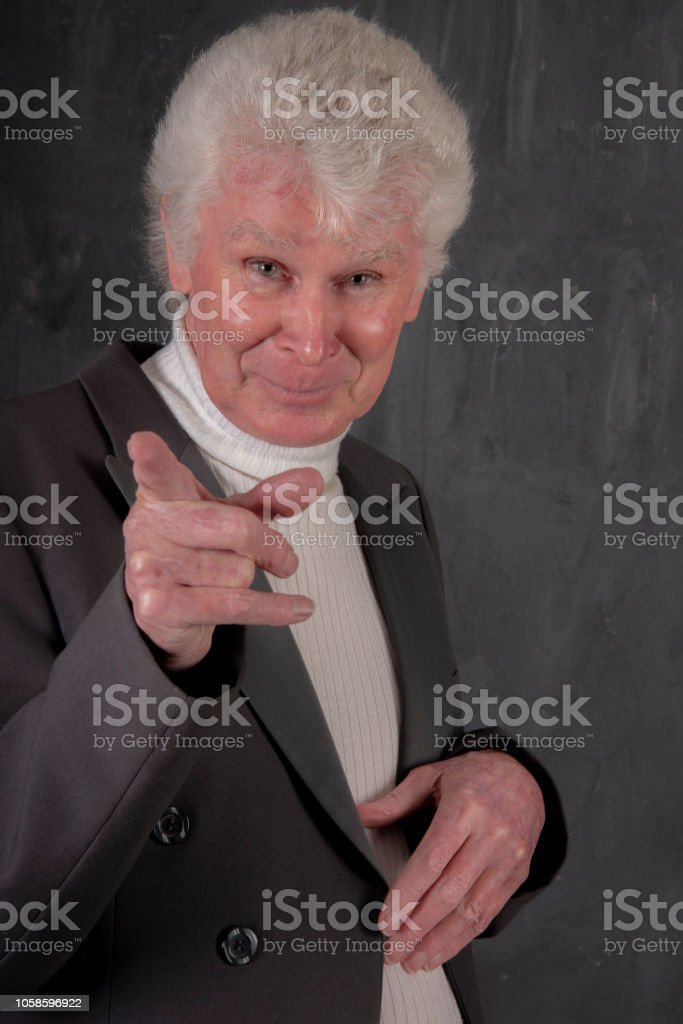 70 year old man points at the camera. stock photo