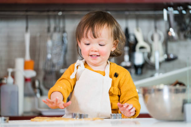 3 year old toddler preparing food and baking in the kitchen stock photo