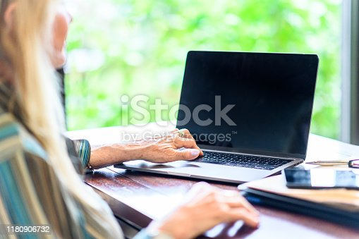 Woman dressed in a business casual blouse sits behind a desk and uses a laptop with a tablet and some paperwork. She is a friendly looking office worker going about her daily  work using a computer and sitting