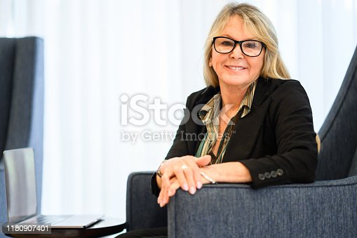 Woman dress in a business casual blouse sits in a chair and uses a laptop with some paperwork. She is a friendly looking office worker going about her daily  work using a computer and sitting in a makeshift office, working on the go or about to have a meeting