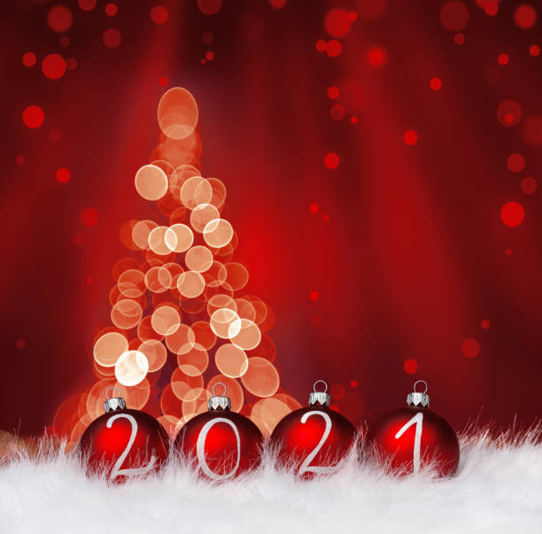 2021 year Red Christmas balls on snow against defocused christmas tree stock photo
