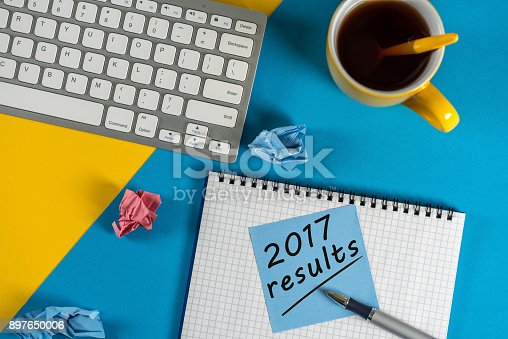 istock 2017 year review on clipboard and coffee against yellow and blue table with keyboard 897650006
