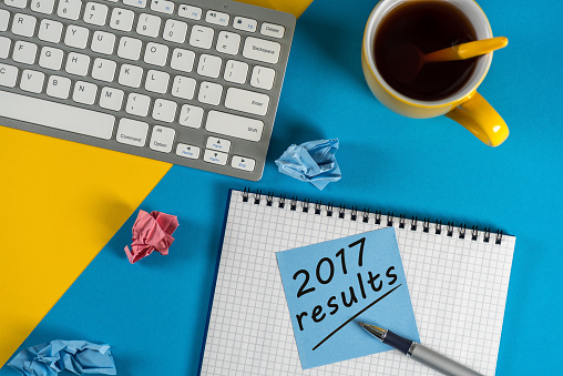 897644798 istock photo 2017 year review on clipboard and coffee against yellow and blue table with keyboard 897650006