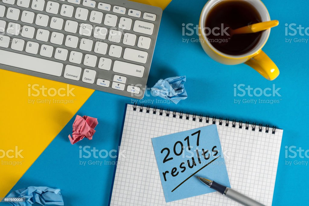 2017 year review on clipboard and coffee against yellow and blue table with keyboard stock photo