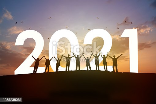Silhouette Group of people rise arm up with 2021 and beautiful sunset background. New year success, Believe and team together concept.