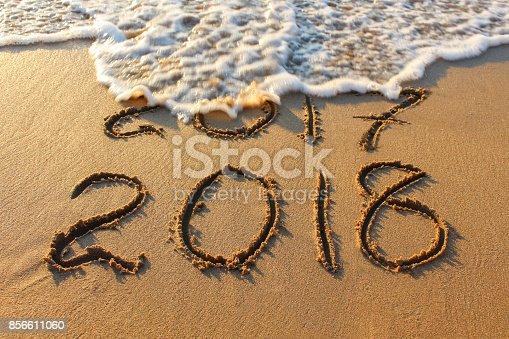 istock 2018 year written on sandy beach sea. Inscription 2017 washes off wave. 856611060