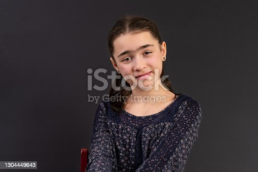 Young girl in yearbook style portrait isolated on a dark background.