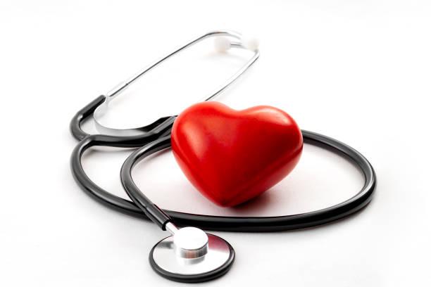 Chequeo de salud anual, medicina de diagnóstico de enfermedades, concepto de salud y Cardiología con corazón rojo y un estetoscopio aislado sobre un fondo blanco hospitalario - foto de stock