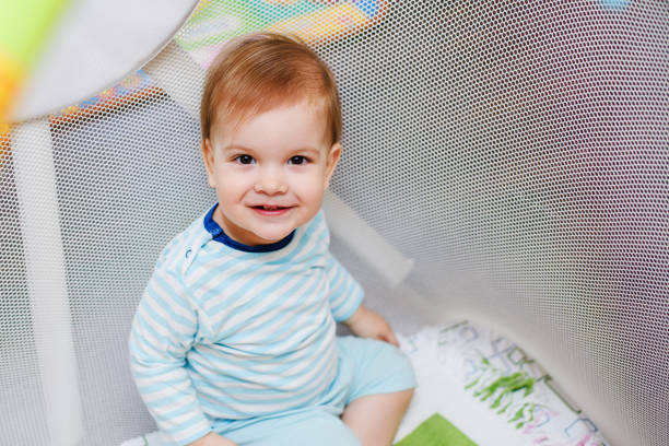 a year-old child is sitting in an arena - playpen stock pictures, royalty-free photos & images