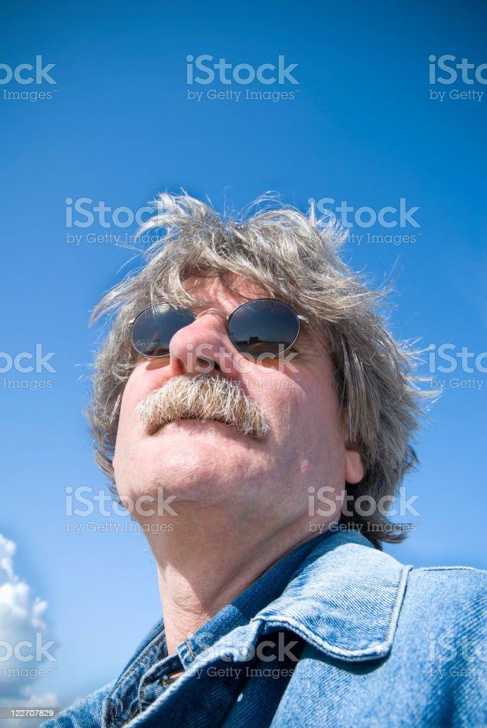 50 year-old man, grey hair, sunglasses, low angle, copy space stok fotoğrafı