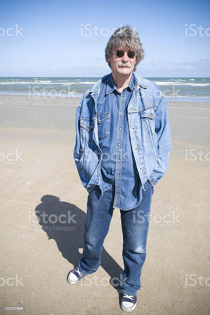 50 year-old man on beach, grey hair, sunglasses, copy space stok fotoğrafı