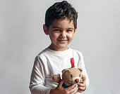 Portrait of 4-5 years adorable old boy playing with soft plush cute bear toy