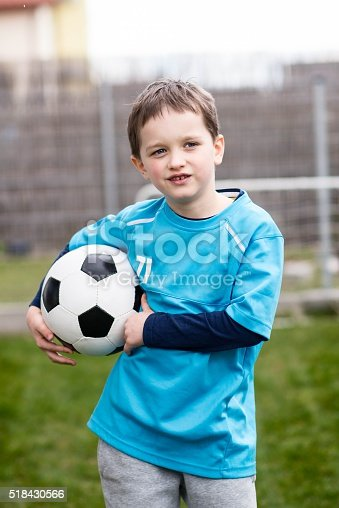 621475196 istock photo 7 years boy - footballer with football ball. 518430566