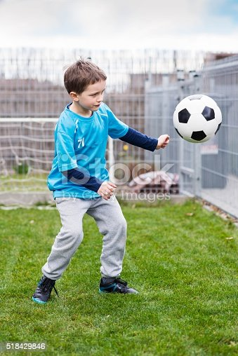 621475196 istock photo 7 years boy kicking ball in the garden. 518429846