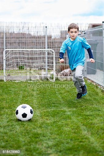 621475196 istock photo 7 years boy kicking ball in the garden. 518429960