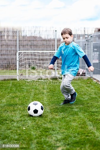 621475196 istock photo 7 years boy kicking ball in the garden. 518430098