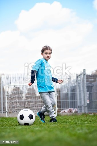 621475196 istock photo 7 years boy kicking ball in the garden. 518430218