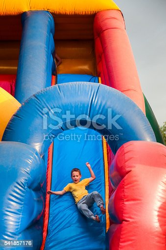 7 years boy play on large colorful inflatable bouncy castle slide