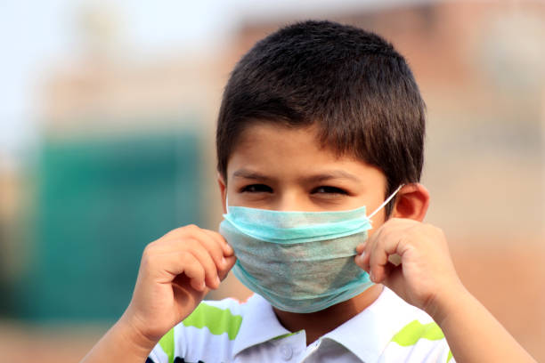 6-7 years boy with pollution mask for protection from virus stock photo