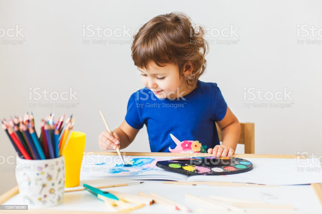 3 years girl painting at the small table at home. Home schooling...