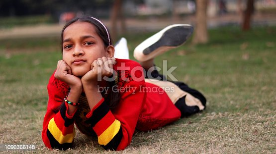 Cute Indian teenage school student portrait outdoors in the nature.