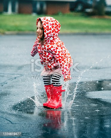 4 years little girl jumping in a puddle of water, Quebec, Canada