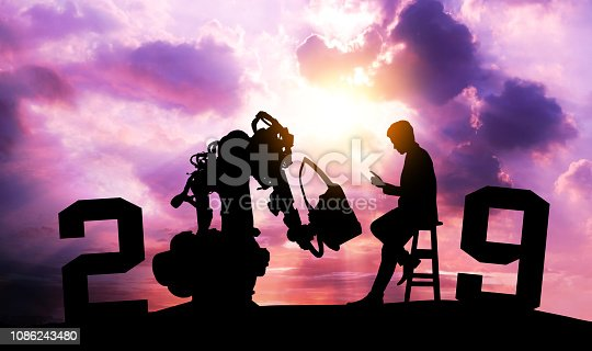 1042088340 istock photo 2019 years of robot assistant technology , industry 4.0 , artificial intelligence trend concept. Silhouette of business man control automation robo advisor arm with sunrise logistic bakckground. 1086243480