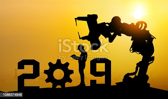 istock 2019 years of robot assistant technology , industry 4.0 , artificial intelligence trend concept. Silhouette of business man control automation robo advisor arm with sunrise logistic bakckground. 1086374948