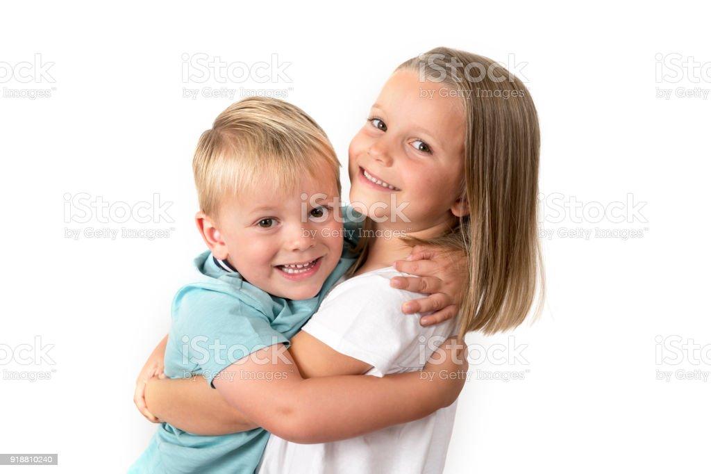 7 Jahre isoliert alte entzückendes blonde glückliches Mädchen posiert mit ihren kleinen 3 Jahre alten Bruder Lächeln fröhlich auf weißem Hintergrund in Kinder und Geschwister-Beziehung-Konzept – Foto